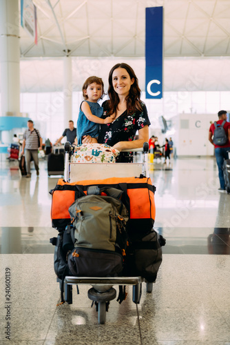 f51ea6f7514b Mother holding a baby girl at the airport and pushing a trolley with ...