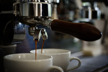 Getting your perfect drink. Coffee being brewed in coffeehouse or cafe. Coffee cups. Small cups to serve hot coffee drink. Brewing coffee with espresso machine. Making espresso with portafilter