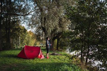Man camping in Estonia, drinking coffee, watching sunrise