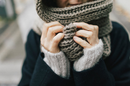 Close up view of woman holding knitted scarf