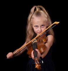 Happy little blond girl learns to play the violin isolated on black