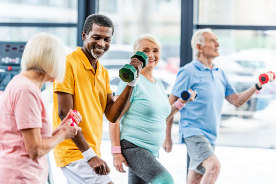 laughing african american man and his friends making exercise with dumbbells at gym