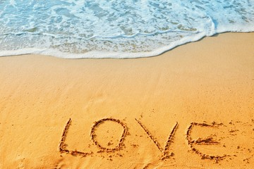 Valentine's Day concept, the word love writing on sand beach with blue waves ocean.