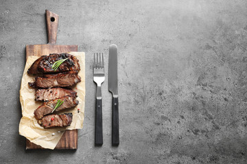 Flat lay composition with delicious barbecued meat served on gray table. Space for text