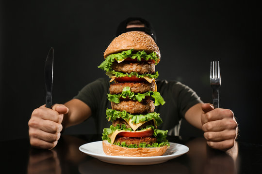 Man with cutlery eating huge burger on black background