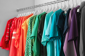 Hangers with different colorful clothes on rack in wardrobe