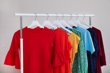 Wardrobe rack with different bright clothes on light background