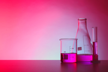 Fototapete - Chemistry laboratory glassware with samples on table against color background
