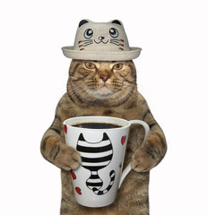 The cat in a funny hat is going to drink a cup of black coffee. White background.