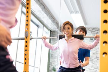 ジムでトレーナーのもとバーベルを持ち上げる女性
