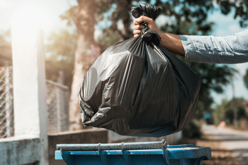woman hand holding garbage black bag put in to trash