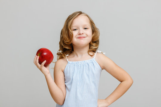 Portrait of a happy smiling little blonde girl on a gray background. Baby eating red apple