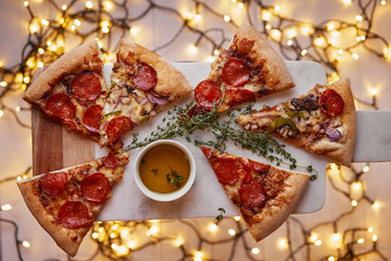 Christmas and New Year atmosphere. Hot Italian pizza with melting tomato, pepperoni and cheese on a white marbel cutting board. Background with lights in bokeh.