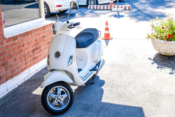 White scooter in the summer Parking lot outside the building