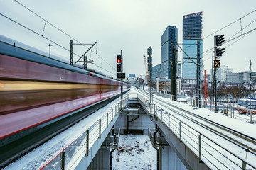 Modern high-speed train moves fast on the business center background at winter evening time.