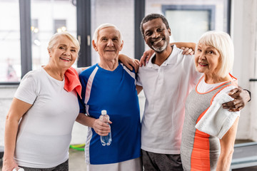 joyful multicultural senior sportspeople looking at camera and embracing each other at gym
