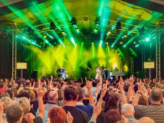 Blick über Publikum auf Bühne eines Retro-Konzert mit grüner Ausleuchtung