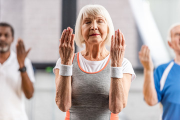selective focus of senior sportswoman with closed eyes making exercise at gym