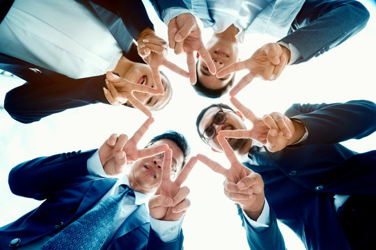 Many young Asian businessmen are working on a big project. And overlapping hands to work together. Many people in the workplace are successful. Close-up of business partners. Happy co working concept