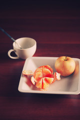 Apple and mandarin on plate. White cup coffie, tea or juice. Healthy food concept. Red tangerine on black wood texture background. Lifestyle. Coffee break. Citrus juice breakfast concept. Top view.