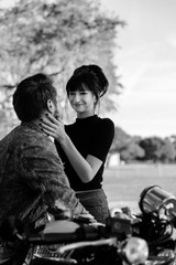 Portrait of two Attractive Good Looking Young Adult Modern Fashionable People Guy Girl Couple on Classic Green Motorcycle Hugging, Kissing, and Looking into each Other's Eyes in Love Black and White