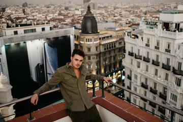 Handsome man on roof near old buildings and huge banner