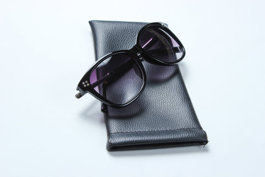 Sunglasses with protective leather case on gray background.