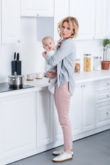 tired mother holding infant baby and looking at camera in kitchen