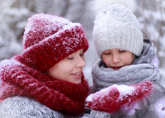 Happy family mother and child daughter having fun, playing at winter walk outdoors.