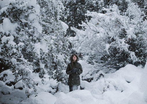 woman hiking in the woods during a snow storm in winter