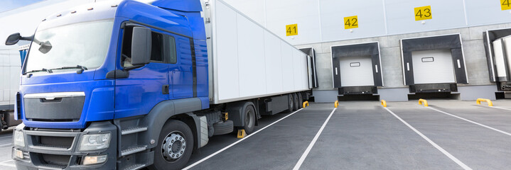 Loading dock of large warehouse with blue cabin truck under loading