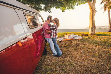 Beautiful middle age caucasian couple kiss and love outdoor in pic nic scene on a meadow with a red old vintgage van used to travel and enjoy the world together forever like a never ending honeymoon