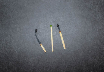 three household matches on a black background.