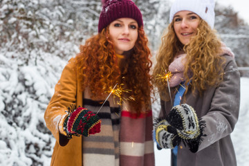 Two young girls sisters are holding sparklers. Curly Caucasian Young Women. In winter clothes and mittens in the park. Christmas concept