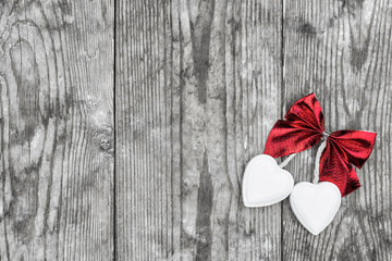 Valentine's Day. Decorative white wooden hearts against an old wooden background.