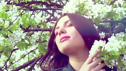 Fotoväggar - Beauty young woman enjoying nature in spring cherry orchard. Happy beautiful girl in garden with blooming trees. Slow motion 4K UHD video footage. 3840X2160