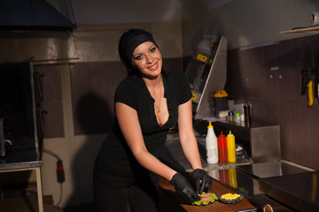 woman chef prepares fresh burgers in the kitchen of the restaurant