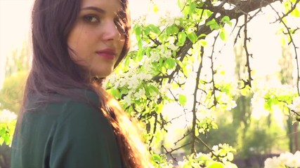 Fotoväggar - Beauty young woman enjoying nature in spring apple orchard. Happy beautiful girl in garden with blooming trees. Slow motion 4K UHD video footage. 3840X2160