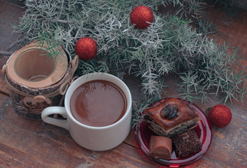 Hot chocolate and sweets on Christmas morning on a wooden background with branches of snow-covered juniper.