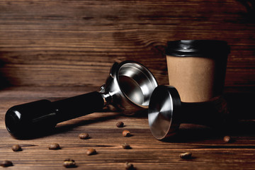 temper portafilter coffee beans cardboard coffee cup on a brown wooden background close-up copy space