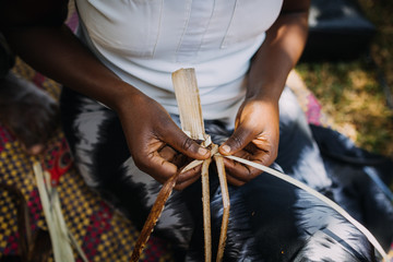 woman weaving banana leaves in Uganda, Africa