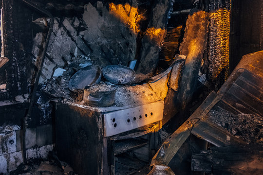 Burnt house interior. Burned kitchen, remains of stove and furniture in black soot