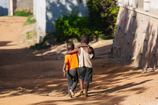 boys walking arm in arm in Uganda, Africa