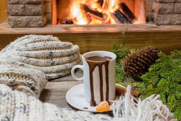 Cozy scene before fireplace with mug of hot chocolate, cones and wool scarf.