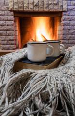 Cozy scene before fireplace with two enameled mugs of tea, a book, and wool scarf.