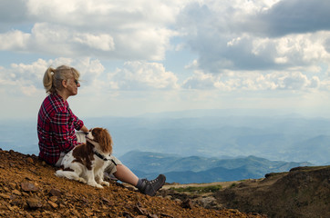 Woman and her dog, Cavalier King Charles Spaniel, dressed in royal stewart, are watching picturesque mountain landscape