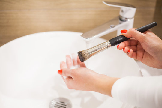Makr up brush. Woman washing dirty makeup brush with soap and foam in the sink
