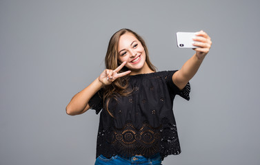 Smiling young girl making selfie photo on smartphone isolated over gray background