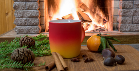 Cozy scene near fireplace with mug of hot drink, tangarine, cones, nuts and cinnamon sricks .