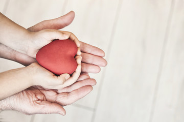 people, age, family, love and health care concept - close up of adult woman and child hands holding red heart over lights background.